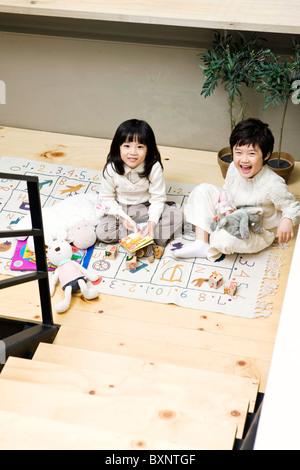 Jungen und Mädchen spielen auf dem Boden - Stockfoto