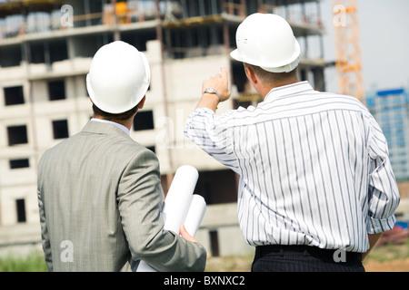 Porträt von Boss zeigt auf Bau mit-Arbeiter in der Nähe von - Stockfoto