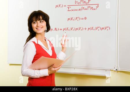 Bild der attraktiven Lehrerin schreiben Formel auf Whiteboard im Unterricht - Stockfoto