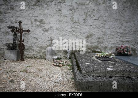 Grab sites mit verlassenen Grabsteine und Kreuze lehnt gegen eine Wand in Cimetière de sterben, Frankreich - Stockfoto
