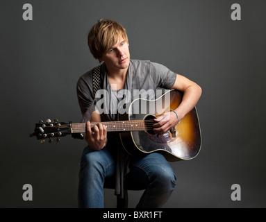junger Mann, eine Gitarre zu spielen - Stockfoto