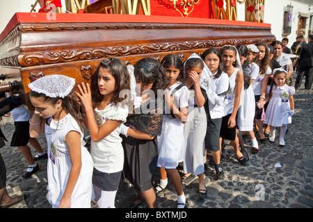 Antigua, Guatemala. Semana Santa (Karwoche). Junge Mädchen tragen ein Anda (Float) in einer religiösen Prozession. - Stockfoto