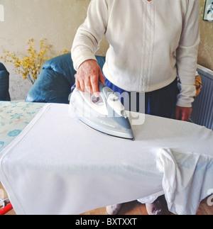 Kaukasische Frau tut ihr Bügeln auf dem Bügelbrett mit Hosenbügler, UK - Stockfoto