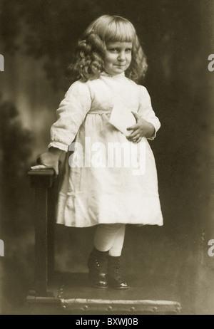 Antikes Bild eines kleinen Jungen mit langen Locken tragen eine dress.c. 1900 - Stockfoto