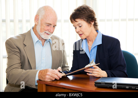 Senior-Unternehmer unterzeichnet einen Vertrag mit Hilfe der eine Reife Geschäftsfrau. - Stockfoto