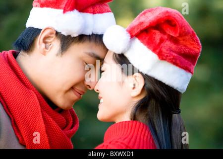 Junge Paar reiben Nasen während Santa Hüte tragen