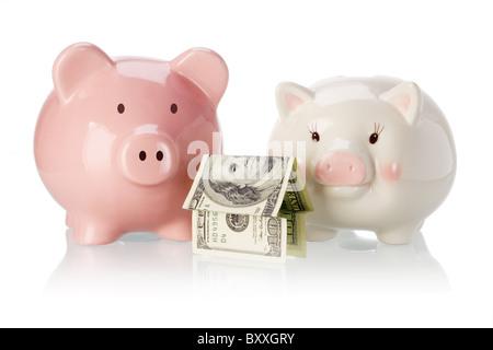 Paar Sparschwein mit Geld Haus auf weißem Hintergrund - Stockfoto