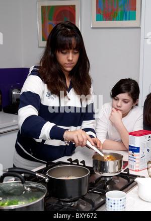 Ein 18yr altes teenage Mädchen Kochen, beobachtet von einem 10yr Mädchen, UK - Stockfoto