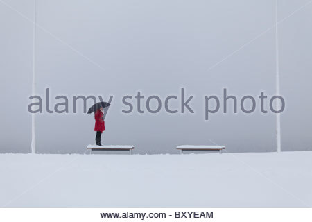 Einsame Figur einer jungen Frau trägt einen roten Mantel hält ein Dach steht auf einer Bank im Schnee - Stockfoto