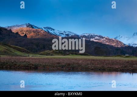 Die aufgehende Sonne leuchtet die schneebedeckten Berge in Elterwater im Great Langdale Valley, Lake district - Stockfoto