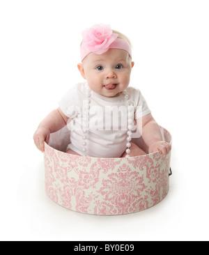 Porträt eines entzückenden Babymädchen mit Zunge heraus sitzen in einem rosa und weißen Hutschachtel tragen ein - Stockfoto