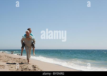 Älteres paar Huckepack auf Strand - Stockfoto