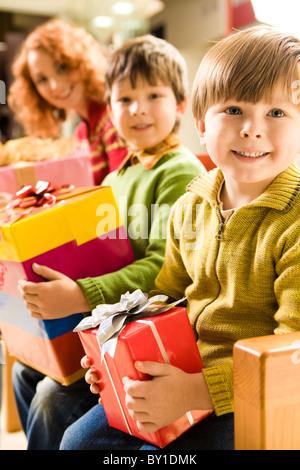 Fröhlicher Junge mit Geschenk in Händen sitzen im Supermarkt auf Grund von seinem Bruder und seiner Mutter - Stockfoto