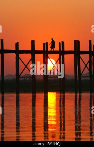 Myanmar (Burma), Amarapura, Taungthaman-See, U Bein Brücke.  Ein Mönch zu Fuß nach Hause bei Sonnenuntergang über - Stockfoto