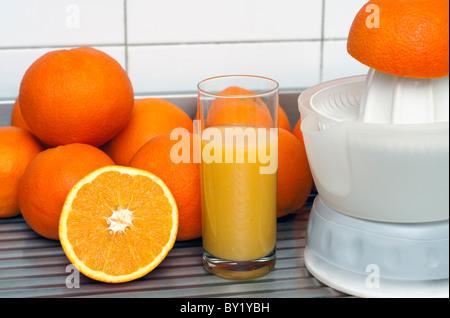 Orangensaft vorbereiten mit einer Saftpresse - Stockfoto