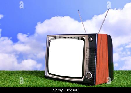 Foto von einem alten Retro-TV im Freien auf dem Rasen mit blauem Himmel und weißen Wolken im Hintergrund - Stockfoto