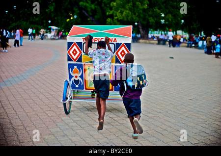 Jungen laufen und schieben Sie einen Erfrischung Warenkorb durch Champs de Mars in Port-au-Prince, Haiti. - Stockfoto