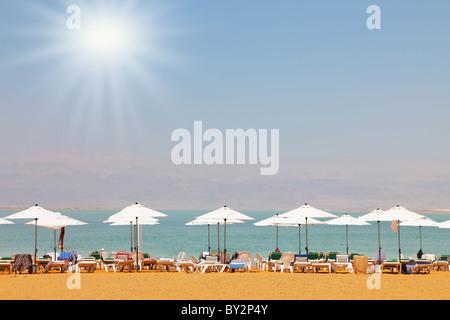 Sonnenliegen, Stühle, Sonnenschirme und Markisen auf den Strand-Luxus-Hotel am Toten Meer in Israel. Sonnigen Frühlingstag - Stockfoto