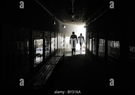 Zwei Männer gehen in dunklen Tunnel Silhouette - Stockfoto