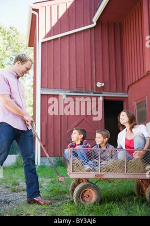 USA, New York, Flandern, Vater ziehen Mutter und zwei Söhne (4-5, 8-9) auf trolley - Stockfoto