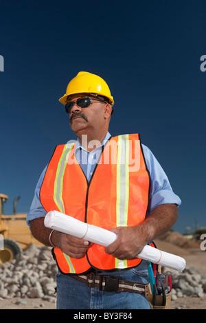 Bau Arbeiter halten Blaupause auf der Baustelle - Stockfoto