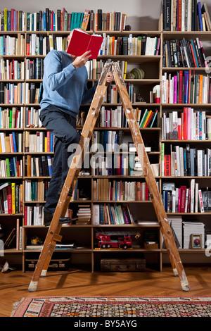 Ein Mann auf einer Leiter in eine Hausbibliothek lesen - Stockfoto
