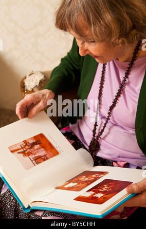 Eine ältere Frau auf der Suche durch ein Fotoalbum - Stockfoto
