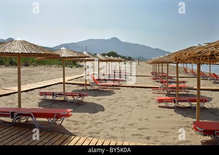 Stroh Sonnenschirme und Stuhlreihen Lounge Sonnenliege am Sandstrand in Griechenland. - Stockfoto