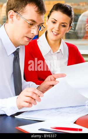 Eine junge vielversprechende Business-Dame der Business-Plan hören von ihrem Chef mit einem Lächeln betrachten - Stockfoto