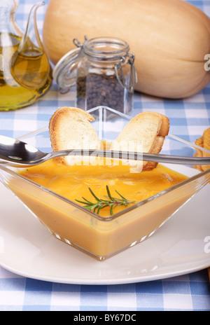 Creme-Kürbis-Suppe in eine quadratische Glasplatte mit geröstetem Brot und Rosmarin - Stockfoto