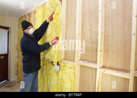 Arbeiter, die Installation von Rockwool Wärmedämmung im Hohlraum des Fachwerk-Wand, UK - Stockfoto