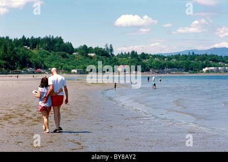 Qualicum Beach, BC, Vancouver Island, British Columbia, Kanada - junges Paar zu Fuß entlang Sandy Seashore - Stockfoto