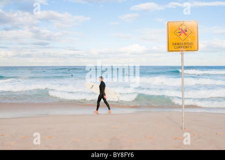 Männliche Surfer geht an Bondi Beach, vorbei an Schilder Warnung vor gefährlichen Strömungen - Stockfoto