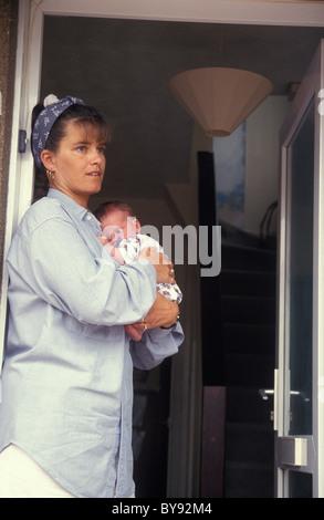 unglückliche Mutter stehend auf offene Tür hält ihr baby - Stockfoto