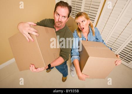 Offensichtlich erschöpft paar Umzugskartons in leeren Raum zu halten. - Stockfoto