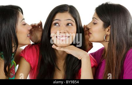 Mädchen in ihren Freunden Ohr flüstern - Stockfoto