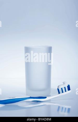 Blaue und weiße Zahnbürste mit Zahnpasta vor ein Wasserglas - Stockfoto