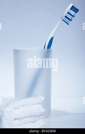 Weißes Handtuch vor einer blau-weißen Zahnbürste in einem Wasserglas - Stockfoto