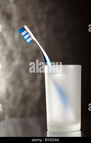 Blaue und weiße Zahnbürste in ein Wasserglas, silberfarben - Stockfoto