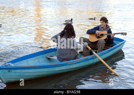 Mann spielt Gitarre im Ruderboot - Stockfoto
