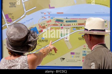 Elegante gut gekleidete Personen suchen in Informationstafel neben Stewards Enclosure, Henley Royal Regatta. Henley. - Stockfoto