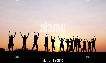 Silhouette indische Mädchen und jungen springen und winken stehend auf einem Reisfeld Paddy bei Sonnenuntergang. - Stockfoto
