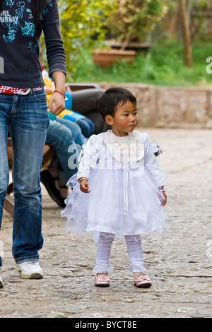 Schöne sehr jungen chinesischen Mädchen lacy weiße Kleid in der Altstadt von Lijiang, Provinz Yunnan, China. JMH4773 - Stockfoto