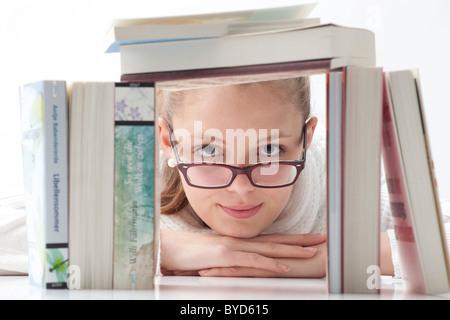Junge Frau mit Brille einen Stapel Bücher durchsehen - Stockfoto