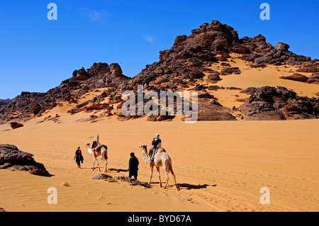 Touristen, Reiten auf Kamelen Mehari der Tuareg-Nomaden, die durch den Sand Plateau Akkakus-Gebirge, Sahara, Libyen - Stockfoto