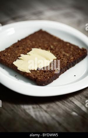 Dunkles Vollkornbrot auf einem weißen Teller mit etwas butter - Stockfoto