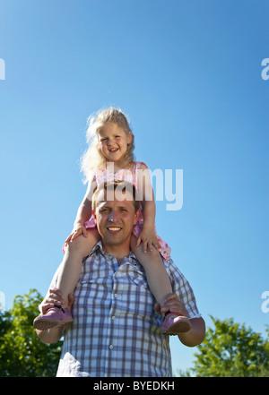 Vater mit seiner Tochter auf seinen Schultern, Lächeln - Stockfoto