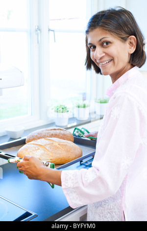 Porträt der Frau hält Brot auf Tablett in Küche - Stockfoto