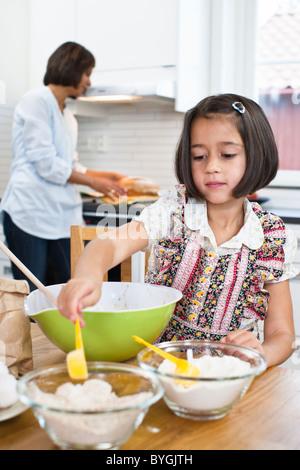 Mädchen mit Mutter im Hintergrund in Küche Backen - Stockfoto