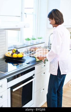 Frau mit Brot auf Tablett in Küche - Stockfoto